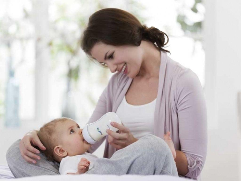 Мама кормит ребёнка смесью